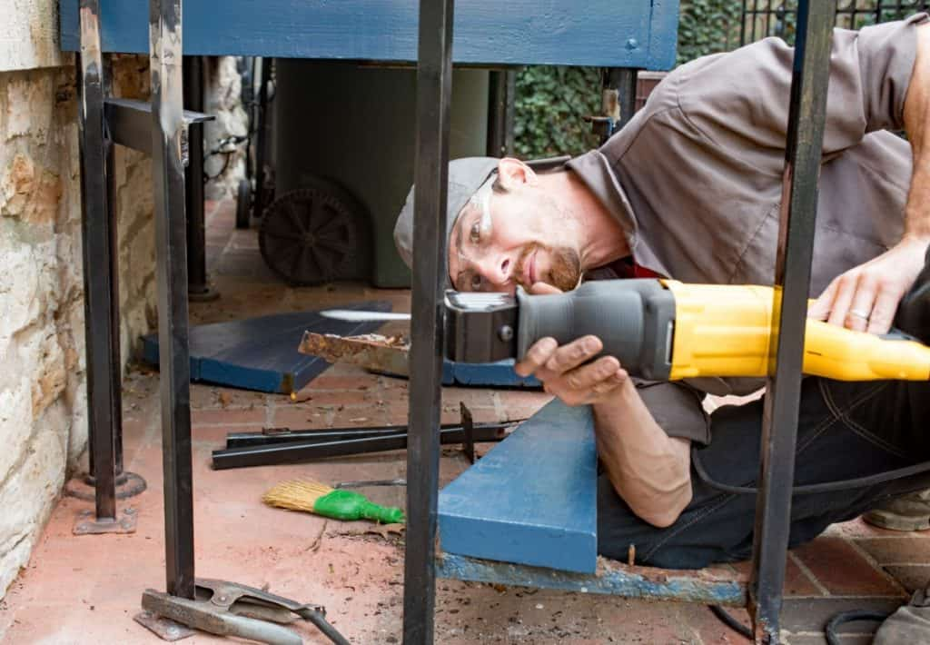 worker using reciprocating saw